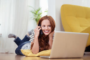 Attractive Young Woman Talking to Someone on Mobile Phone While Relaxing at the Living Room with Laptop Computer-1