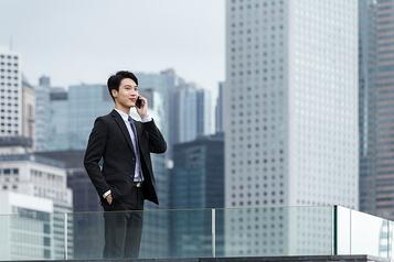 Businessman talk to mobile phone with business background