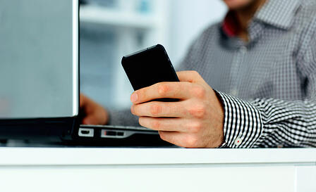Close-up of male hand holding smartphone and typing on a laptop keyboard