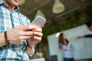 Closeup of hands of young man in checkered shirt using mobile phone while his partners arguing.jpeg