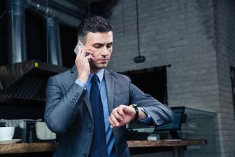 Confident businessman speaking on the phone and looking on the wristwatch in cafe