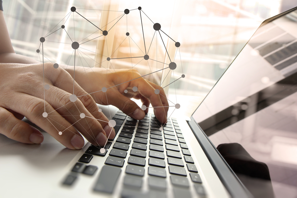 Double exposure of business man hand working on blank screen laptop computer on wooden desk as concept with social media diagram