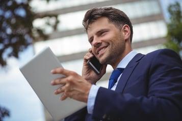 Handsome businessman holding digital tablet and talking on mobile phone.jpeg