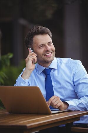 Handsome businessman talking on mobile phone while using laptop at outdoor cafx96xA7