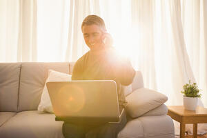 Happy man sitting on couch phoning and using laptop at home in the living room