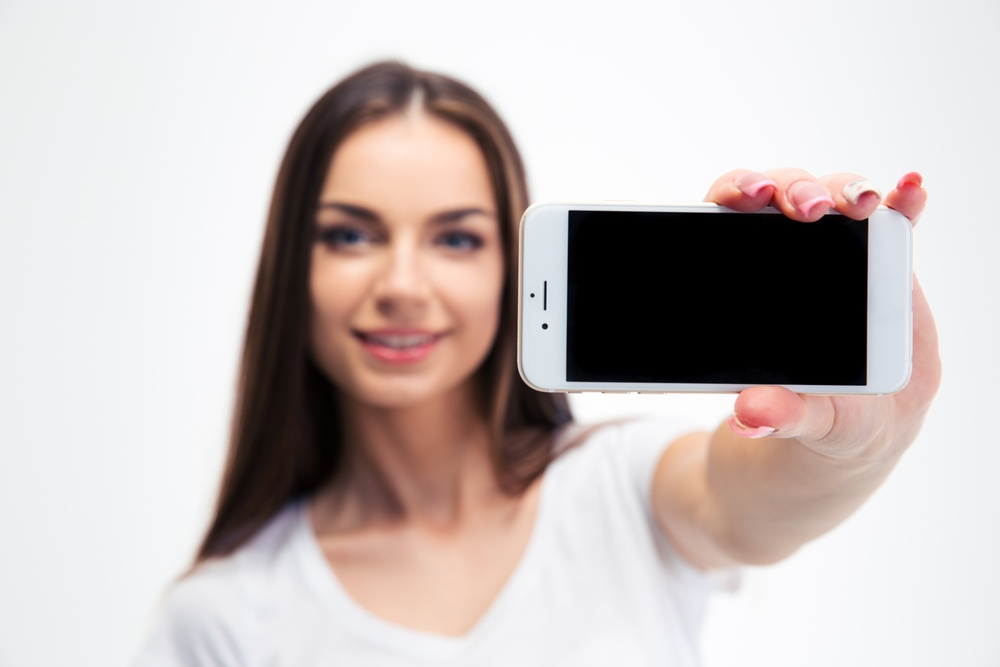 Happy young woman showing blank smartphone screen isolated on a white background. Looking at camera. Focus on smartphone