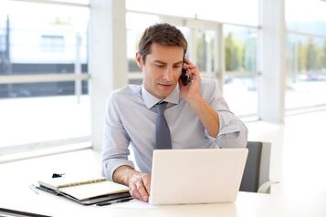 Portrait of businessman talking on mobile phone in office-1