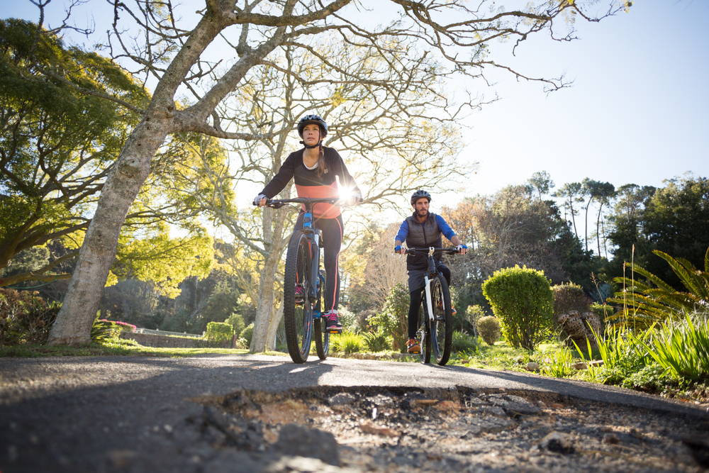Smiling biker couple cycling on the countryside road