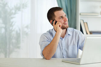 Young businessman with his cellphone in his home office