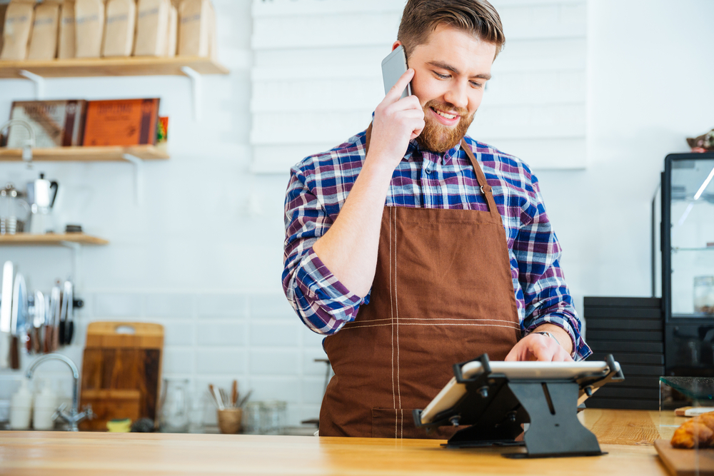 Handsome smiling barista with beard taking order on cell phone and using tablet in cafeteria
