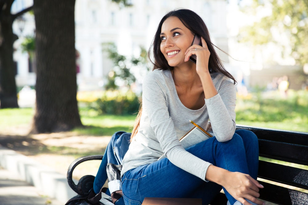 Portrait of a happy woman sitting on the bench and talking on the phone outdoors