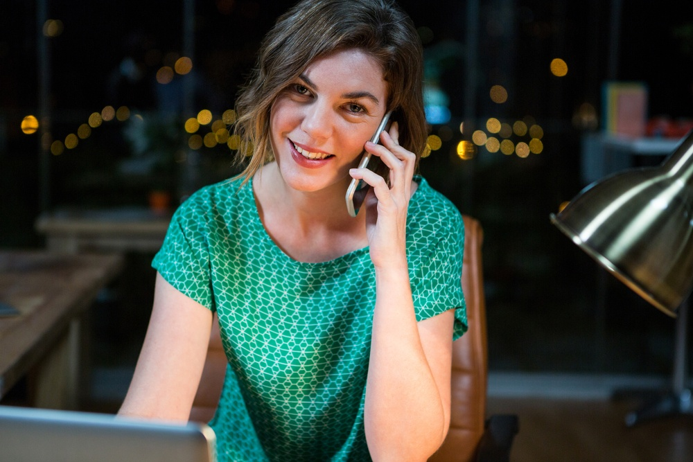 Portrait of businesswoman talking on mobile phone while working on laptop in the office